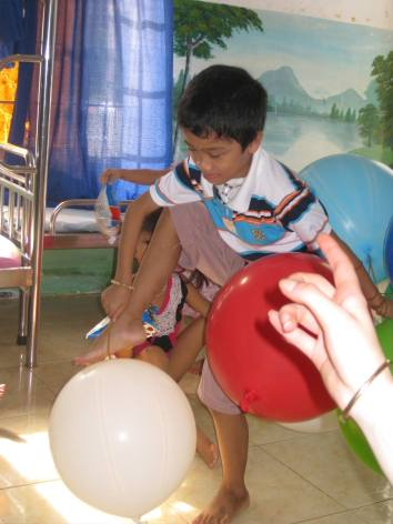 Huy Anh gathering balloons. He is HIV but his throat cancer is what will take him from us in 3-4 months.